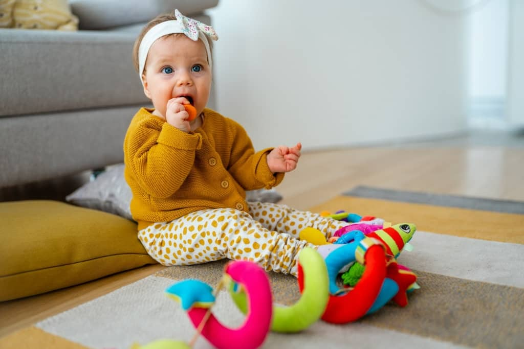 Adorable baby playing with colorful toy at home