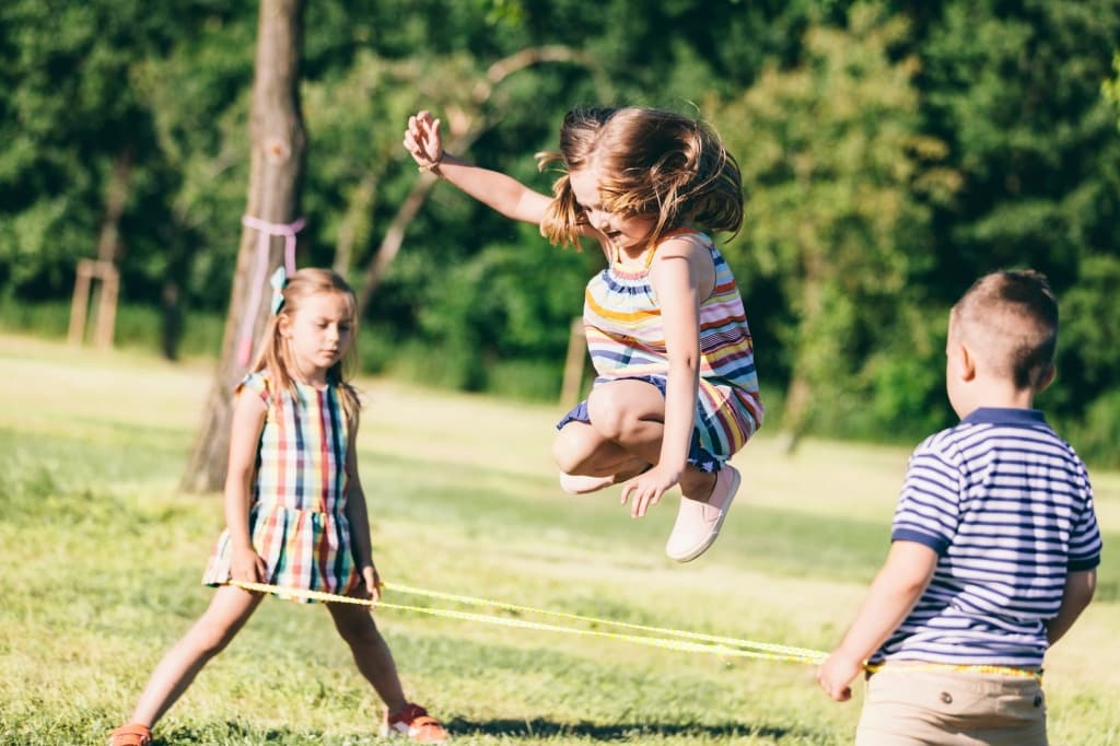 Little girl jumping through the elastic, playing with other children.