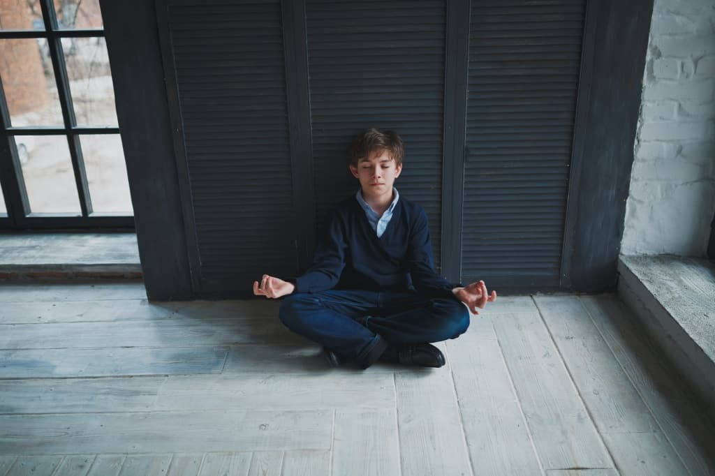 Calm teenager boy sitting on the floor near the dark blue walls in the room in Lotus position