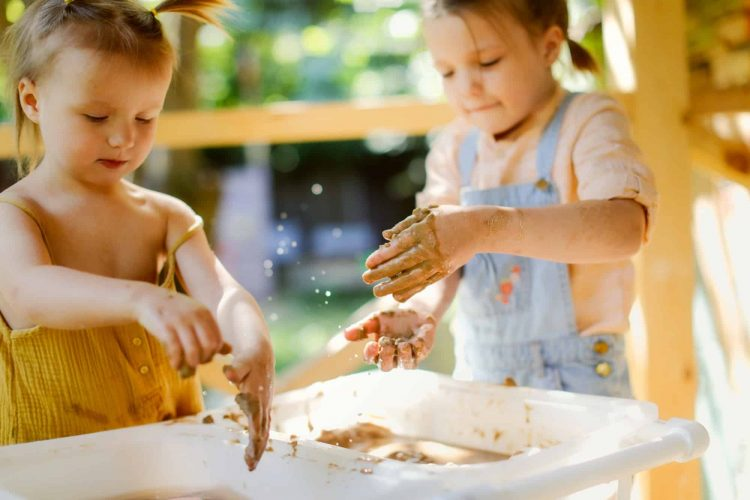 Happy children play with sand and water in sensory baskets on the outdoor sensory table,