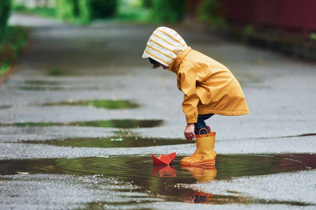 Kid in yellow waterproof cloak and boots playing outdoors after the rain
